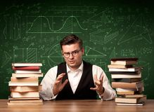 Teacher explaining concept. A young passionate male teacher sitting at school desk, reading a book, with area algorythm calculations and numbers on the Stock Image