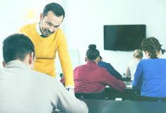Teacher explaining difficult problem to student. Teacher explaining a difficult problem to student during test at a class Royalty Free Stock Image