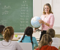 Teacher explaining globe to students. Teacher stands at the front of a class and holds a globe Royalty Free Stock Photography
