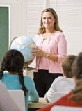 Teacher explaining globe to students Royalty Free Stock Photo