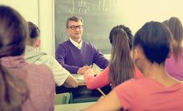 Teacher explaining the math near chalkboard. Senior male teacher near the chalkboard explaining the math at the lesson royalty free stock photos