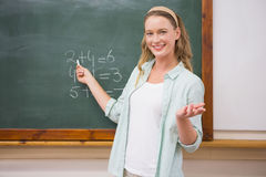 Teacher explaining maths in blackboard. At elementary school Stock Photos
