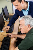Teacher Explaining Senior Man In Computer Class Royalty Free Stock Images