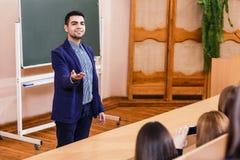 Teacher explaining something to students. Young teacher explaining something to students in classroom Stock Image