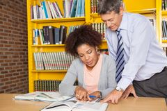 Teacher Explaining Student In College Library. Mature male teacher explaining student at table in college library Stock Images
