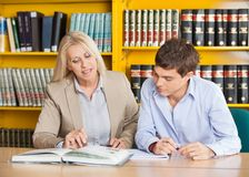 Teacher Explaining Student While Sitting At Table. Mature female teacher explaining student while sitting at table in university library Stock Photography