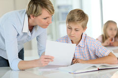 Teacher explaining to pupil the excercise. Teacher showing paper to pupil in class Royalty Free Stock Photos
