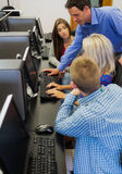 Teacher explaining to students in computer room Stock Images