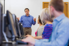 Teacher explaining to students in computer room Stock Photos