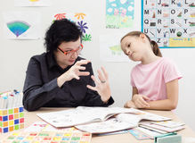 Teacher explains lesson to child in gesture Royalty Free Stock Image