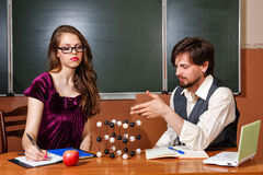 Teacher explains structure of crystal lattice of student. Stock Image