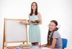 Teacher explains topic of lesson at blackboard Royalty Free Stock Image