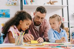 Teacher in eyeglasses helping multicultural preschoolers with drawing at table. In classroom stock photo