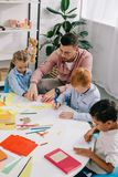 Teacher in eyeglasses helping multicultural preschoolers with drawing at table. In classroom stock photography