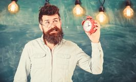 Teacher in eyeglasses holds alarm clock. Bearded hipster holds clock, chalkboard on background, copy space. Man with. Beard and mustache on annoyed face listens royalty free stock photography
