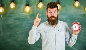 Teacher in eyeglasses holds alarm clock. Bearded hipster holds clock, warning with index finger, copy space. Discipline. Concept. Man with beard and mustache on stock photo