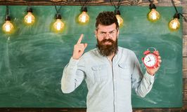 Teacher in eyeglasses holds alarm clock. Discipline concept. Bearded hipster holds clock, warning with index finger stock images