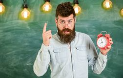 Teacher in eyeglasses holds alarm clock. Discipline concept. Man with beard and mustache on strict face stand in. Classroom. Bearded hipster holds clock royalty free stock images