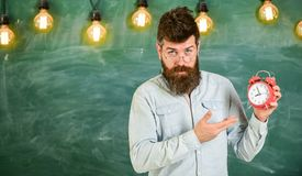 Teacher in eyeglasses holds alarm clock. Discipline concept. Man with beard and mustache on strict face stand in. Classroom. Bearded hipster holds clock royalty free stock photo