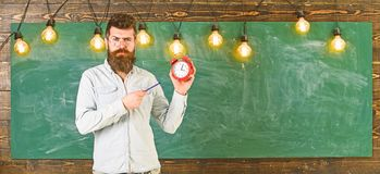 Teacher in eyeglasses holds alarm clock and pen. Bearded hipster holds clock, chalkboard on background, copy space. Man. With beard and mustache on strict face royalty free stock image