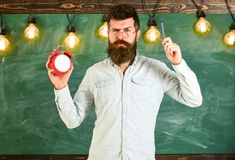 Teacher in eyeglasses holds alarm clock and pen. Discipline concept. Bearded hipster holds clock, chalkboard on. Background. Man with beard and mustache on stock photo