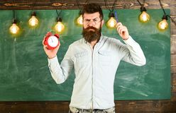 Teacher in eyeglasses holds alarm clock and pen. Discipline concept. Man with beard and mustache on strict face stands. In classroom. Bearded hipster holds stock photography