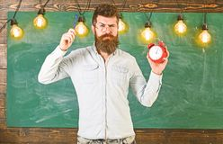 Teacher in eyeglasses holds alarm clock and pen. Discipline concept. Man with beard and mustache on strict face stands. In classroom. Bearded hipster holds royalty free stock photos