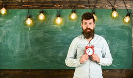 Teacher in eyeglasses holds alarm clock. Schedule and regime concept. Bearded hipster holds clock, chalkboard on. Background, copy space. Man with beard and Royalty Free Stock Photography