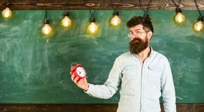 Teacher in eyeglasses holds alarm clock. Schedule and regime concept. Man with beard and mustache on confused face in. Classroom. Bearded hipster holds clock stock photo