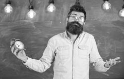 Teacher in eyeglasses holds alarm clock. Schedule and regime concept. Man with beard and mustache on confused face. Expression in classroom. Bearded hipster stock images