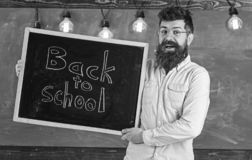 Teacher in eyeglasses holds blackboard with title back to school. Education and studying concept. Man with beard and. Mustache on happy face welcomes students stock photography
