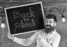 Teacher in eyeglasses holds blackboard with title back to school. Man with beard and mustache on happy face welcomes. Colleagues, chalkboard on background stock images
