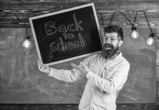 Teacher in eyeglasses holds blackboard with title back to school. Man with beard and mustache on happy face welcomes. Students, chalkboard on background. High royalty free stock photography