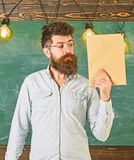 Teacher in eyeglasses holds book in hand, copy space. Man with beard and mustache on calm face stands in classroom. Scientist holds book, chalkboard on royalty free stock images