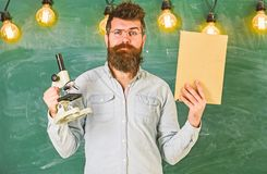 Teacher in eyeglasses holds book and microscope. Man with beard and mustache on strict face in classroom. Scientist. Holds book and microscope, chalkboard on stock images