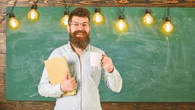 Teacher in eyeglasses holds book and mug of coffee or tea. Coffee break concept. Man with beard on happy face in. Classroom. Scientist holds book and mug of stock photo