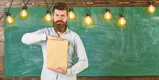 Teacher in eyeglasses presenting blank book. Bearded hipster holds book, chalkboard on background. Man with beard and. Mustache on strict face stand in stock photography