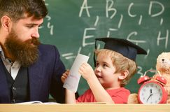 Teacher, father checking homework, helps to boy, son. Individual studying concept. Teacher in formal wear and pupil in. Mortarboard in classroom, chalkboard on royalty free stock photo