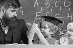Teacher, father checking homework, helps to boy, son. Individual studying concept. Teacher in formal wear and pupil in. Mortarboard in classroom, chalkboard on royalty free stock image