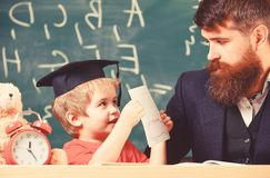 Teacher, father checking homework, helps to boy, son. Individual studying concept. Teacher in formal wear and pupil in. Mortarboard in classroom, chalkboard on stock image