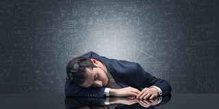 Teacher fell asleep at his workplace with full draw blackboard concept. Elegant teacher fell asleep at his workplace with full draw blackboard concept royalty free stock photography
