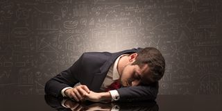 Teacher fell asleep at his workplace with full draw blackboard concept. Elegant teacher fell asleep at his workplace with full draw blackboard concept royalty free stock photo