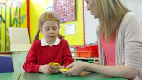 Teacher And Female Pupil Playing Number Game At Desk stock footage