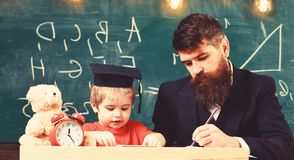 Teacher in formal wear and pupil in mortarboard in classroom, chalkboard on background. Father checking homework, helps royalty free stock photos