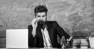 Teacher formal wear sit table classroom chalkboard background. Teacher concentrated bearded mature schoolmaster. Listening with attention. Teacher listening stock photos