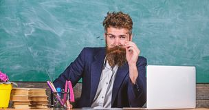 Teacher formal wear sit table classroom chalkboard background. Teacher concentrated bearded mature schoolmaster. Listening with attention. Teacher listening royalty free stock images