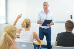 Teacher in front class student with arm raised Royalty Free Stock Photos