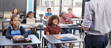 Teacher in front of school class, back view, panoramic Royalty Free Stock Photos