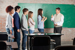 Teacher Gesturing Thumbsup Sign To Successful. Female student with classmates standing in row at classroom Royalty Free Stock Images