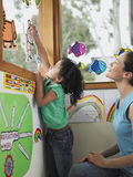 Teacher And Girl Decorating Window With Cutout Drawings Royalty Free Stock Photos
